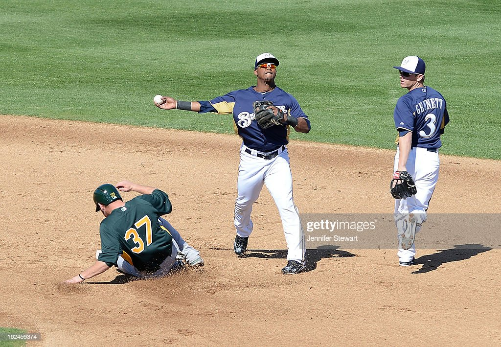 Infielder <a gi-track='captionPersonalityLinkClicked' href=/galleries/search?phrase=Jean+Segura&family=editorial&specificpeople=7521808 ng-click='$event.stopPropagation()'>Jean Segura</a> #9 of the Milwaukee Brewers attempts to turn the play to first base as <a gi-track='captionPersonalityLinkClicked' href=/galleries/search?phrase=Brandon+Moss&family=editorial&specificpeople=702783 ng-click='$event.stopPropagation()'>Brandon Moss</a> #37 of the Oakland Athletics slides into second base in the spring training game at Maryvale Baseball Park on February 23, 2013 in Phoenix, Arizona.