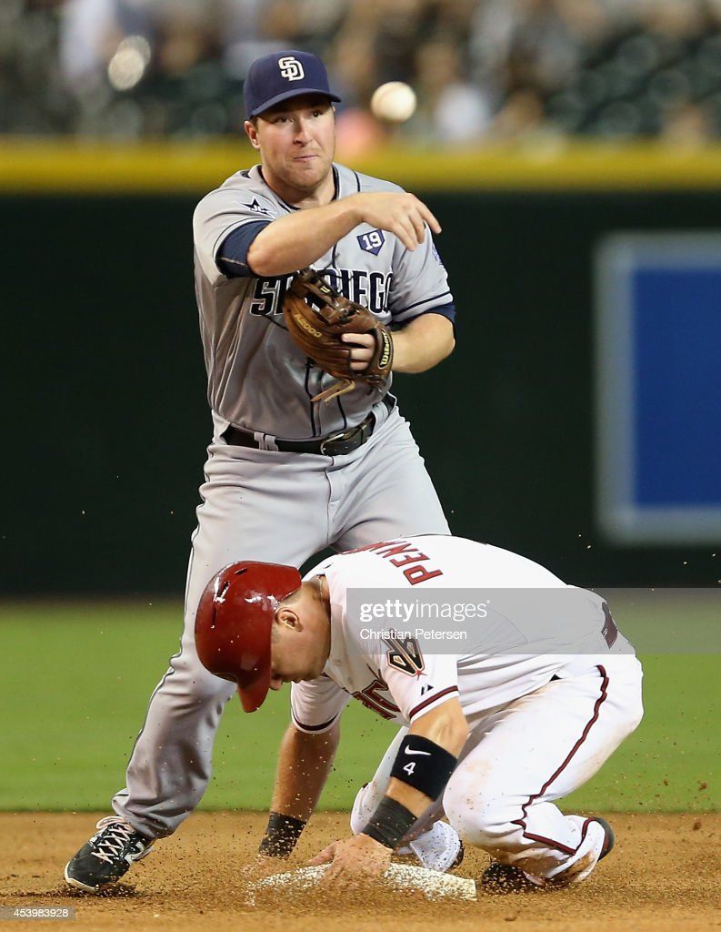 Infielder Jedd Gyorko of the San Diego Padres throws over Cliff Pennington of the Arizona Diamondbacks after getting a force out at second base...