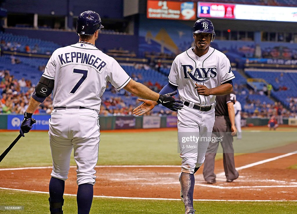 Infielder <a gi-track='captionPersonalityLinkClicked' href=/galleries/search?phrase=Jeff+Keppinger&family=editorial&specificpeople=835796 ng-click='$event.stopPropagation()'>Jeff Keppinger</a> #7 of the Tampa Bay Rays congratulates <a gi-track='captionPersonalityLinkClicked' href=/galleries/search?phrase=B.J.+Upton&family=editorial&specificpeople=810704 ng-click='$event.stopPropagation()'>B.J. Upton</a> #2 after he scored against the Boston Red Sox during the game at Tropicana Field on September 18, 2012 in St. Petersburg, Florida.