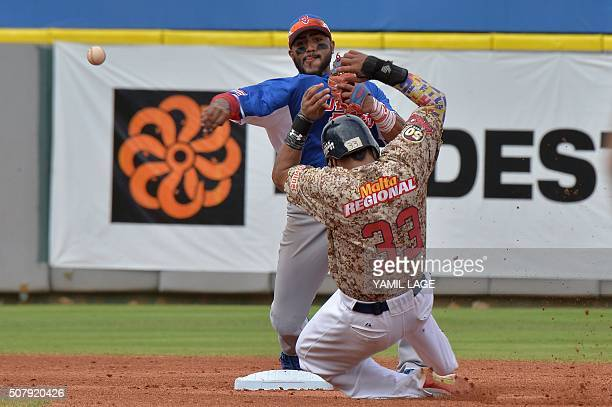 Infielder Jesmuel Valentin at Puerto Rico makes an out on second base against Juniel Alberto Querecuto of Venezuela during their 2016 Caribbean...