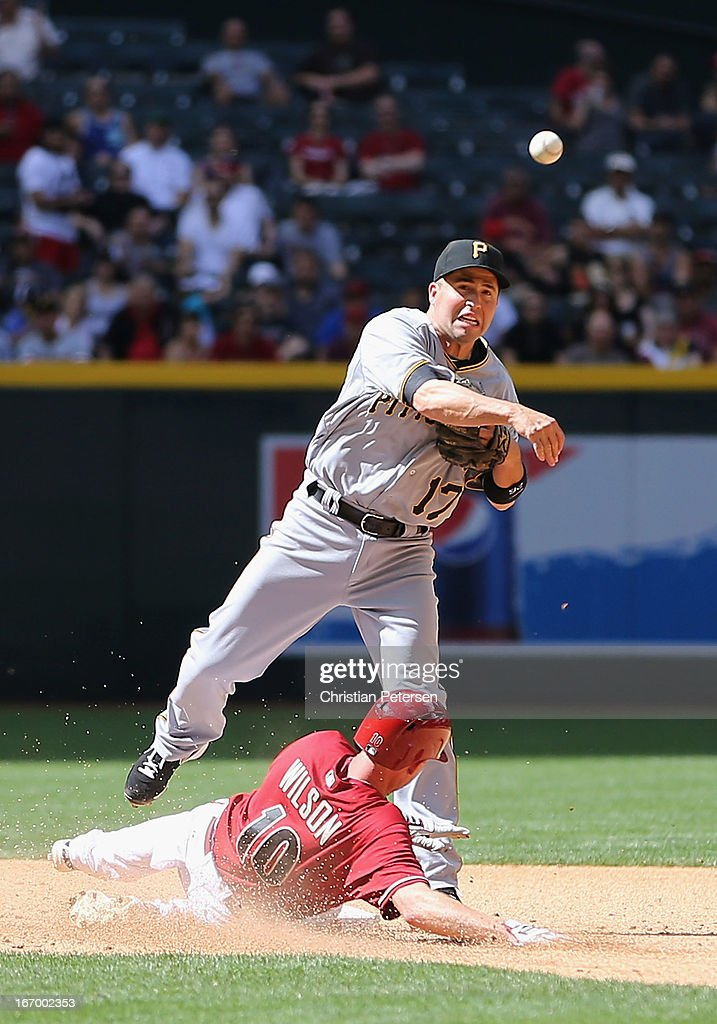 Infielder <a gi-track='captionPersonalityLinkClicked' href=/galleries/search?phrase=John+McDonald+-+Baseball+Player&family=editorial&specificpeople=215395 ng-click='$event.stopPropagation()'>John McDonald</a> #17 of the Pittsburgh Pirates throws over the sliding Josh Wilson #10 of the Arizona Diamondbacks during the MLB game at Chase Field on April 10, 2013 in Phoenix, Arizona. The Diamondbacks defeated the Pirates 10-2.