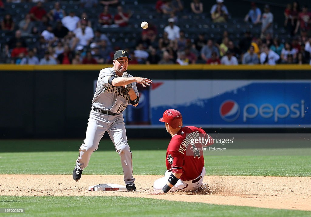 Infielder <a gi-track='captionPersonalityLinkClicked' href=/galleries/search?phrase=John+McDonald+-+Baseball+Player&family=editorial&specificpeople=215395 ng-click='$event.stopPropagation()'>John McDonald</a> #17 of the Pittsburgh Pirates throws over the sliding Cliff Pennington #4 of the Arizona Diamondbacks during the MLB game at Chase Field on April 10, 2013 in Phoenix, Arizona. The Diamondbacks defeated the Pirates 10-2.