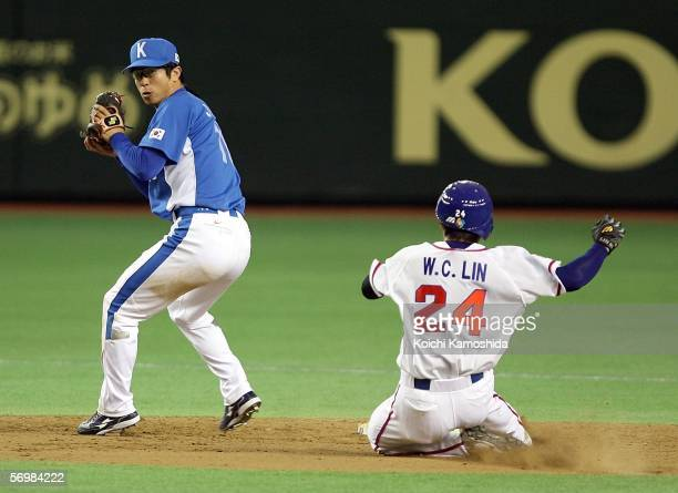 Infielder JongKook Kim of Korea throws the ball while outfielder WeiChu Lin of Chinese Taipei slides to base during the 2006 World Baseball Classic...