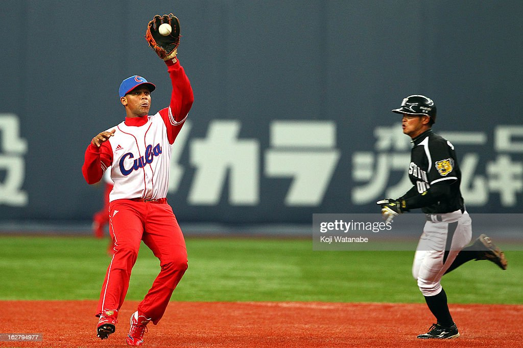 Infielder Jose Fernandez #8 of Cuba reaches for the ball during the friendly game between Hanshin Tigers and Cuba at Kyocera Dome Osaka on February 27, 2013 in Osaka, Japan.