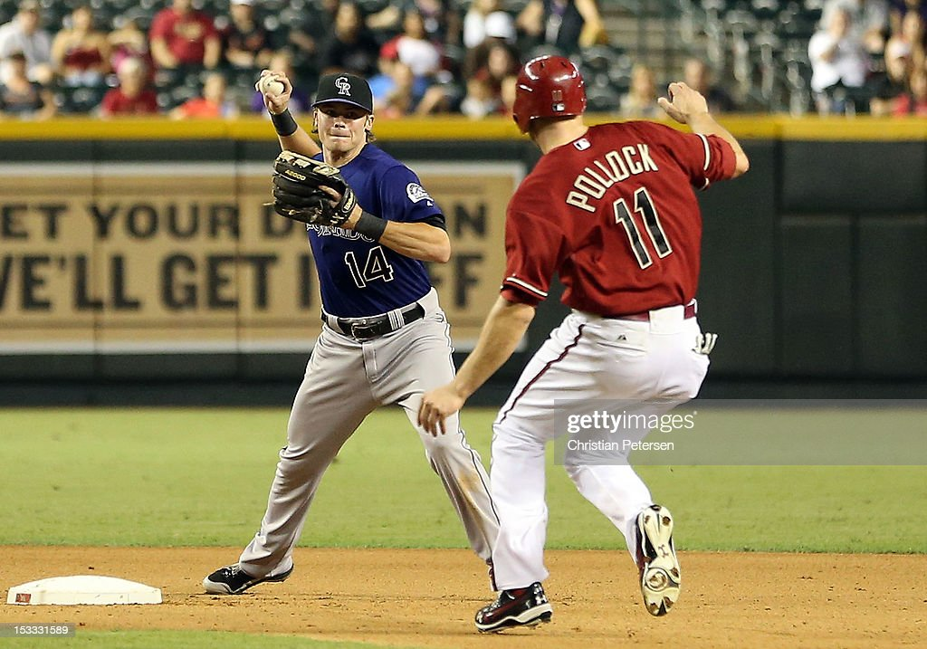 Infielder Josh Rutledge #14 of the Colorado Rockies throws over A.J. Pollock #11 of the Arizona Diamondbacks to complete a double play during the seventh inning of the MLB game at Chase Field on October 3, 2012 in Phoenix, Arizona.