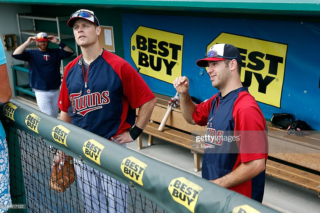 Infielder Justin Morneau #33 and catcher Joe Mauer #7 of the Minnesota Twins talk with fans just before the start of the Grapefruit League Spring Training Game against the Toronto Blue Jays at Hammond Stadium on March 24, 2013 in Fort Myers, Florida.