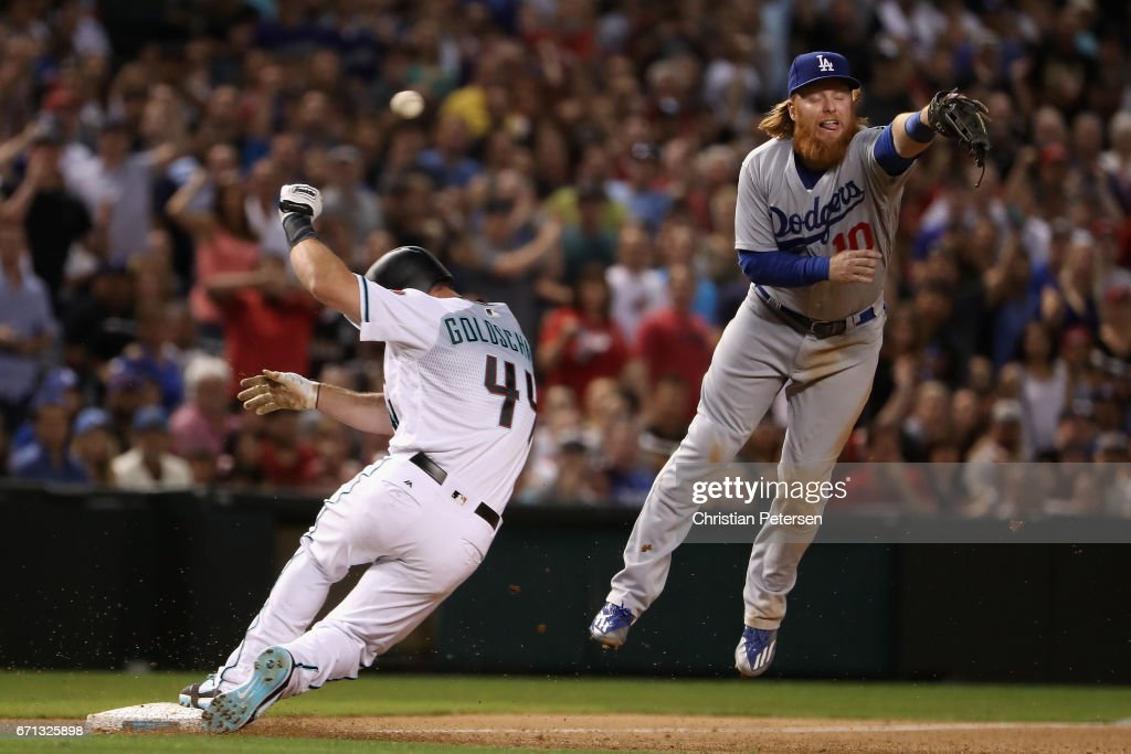 Infielder Justin Turner #10 of the Los Angeles Dodgers is unable to catch the throw as Paul Goldschmidt #44 of the Arizona Diamondbacks slides into third base during the seventh inning of the MLB game at Chase Field on April 21, 2017 in Phoenix, Arizona.