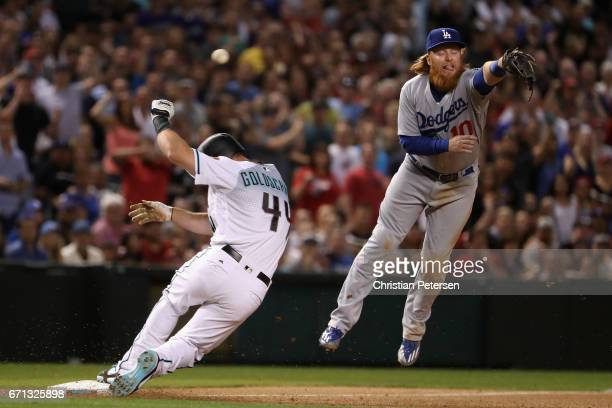 Infielder Justin Turner of the Los Angeles Dodgers is unable to catch the throw as Paul Goldschmidt of the Arizona Diamondbacks slides into third...