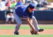Infielder Kensuke Tanaka of the Texas Rangers fields an infield single hit by Willie Bloomquist of the Seattle Mariners during the first inning of...