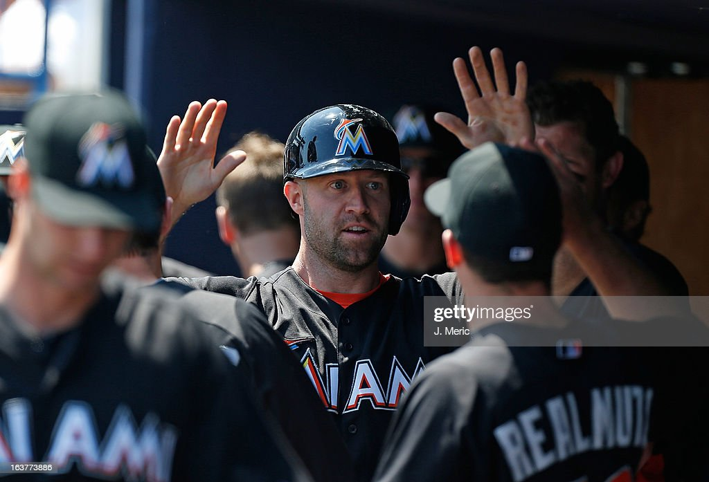 Infielder Kevin Kouzmanoff #15 of the Miami Marlins is congratulated after scoring against the New York Yankees during a Grapefruit League Spring Training Game at George M. Steinbrenner Field on March 15, 2013 in Tampa, Florida.