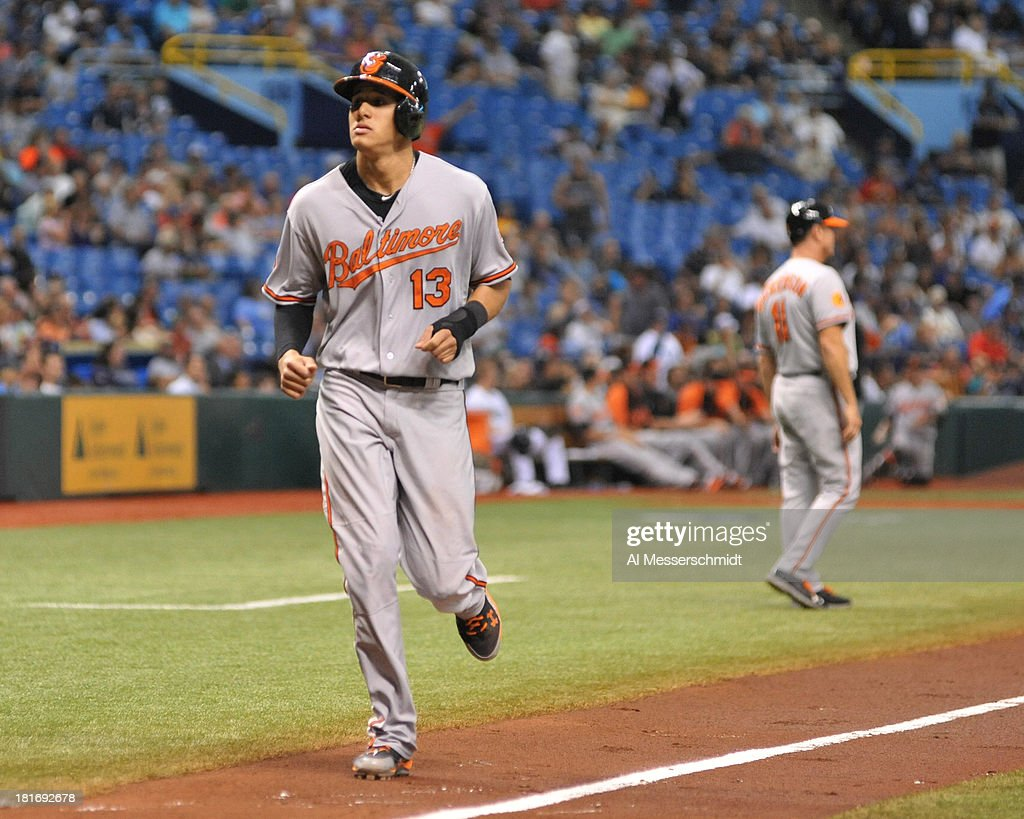 Infielder Manny Machado #13 of the Baltimore Orioles scores in the 4th inning after a home run by infielder Chris Davis #19 against the Tampa Bay Rays September 23, 2013 at Tropicana Field in St. Petersburg, Florida.