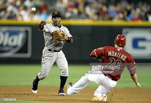 Infielder Miguel Tejada of the San Francisco Giants throws over the sliding Miguel Montero of the Arizona Diamondbacks to complete a double play...