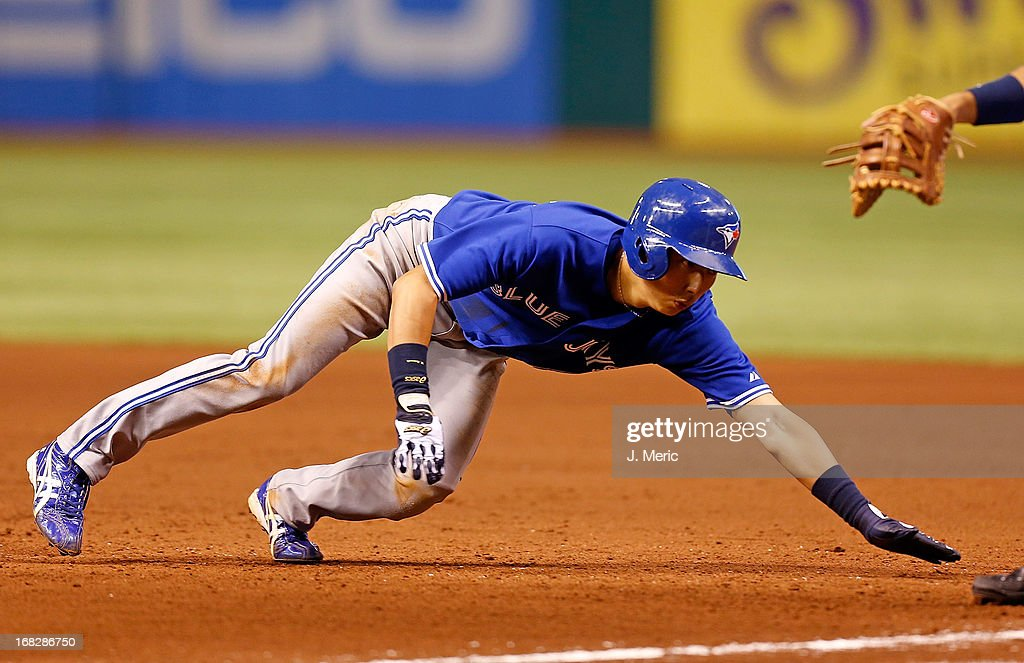 Infielder Munenori Kawasaki #66 of the Toronto Blue Jays dives back to first base against the Tampa Bay Rays during the game at Tropicana Field on May 7, 2013 in St. Petersburg, Florida.