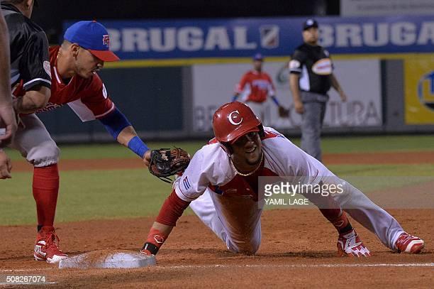 Infielder Neftali Soto of Puerto Rican slides safe at first base against Yulieski Gourriel of Cuban during their 2016 Caribbean baseball series game...