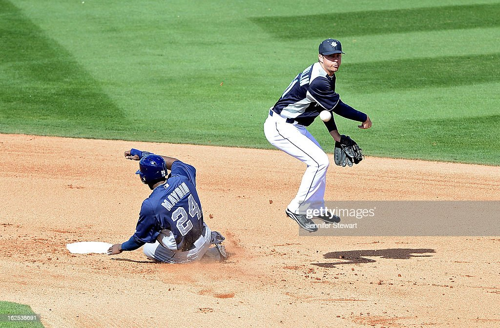 Infielder Nick Franklin #61 of the Seattle Mariners turns a double over the sliding <a gi-track='captionPersonalityLinkClicked' href=/galleries/search?phrase=Cameron+Maybin&family=editorial&specificpeople=2364846 ng-click='$event.stopPropagation()'>Cameron Maybin</a> #24 of the San Diego Padres during the spring training game at Peoria Sports Complex on February 24, 2013 in Peoria, Arizona.