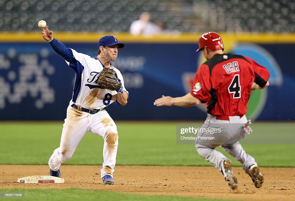 Infielder Nick Punto of Italy throws over Pete Orr of Canada to complete a double play during the eighth inning of the World Baseball Classic First...