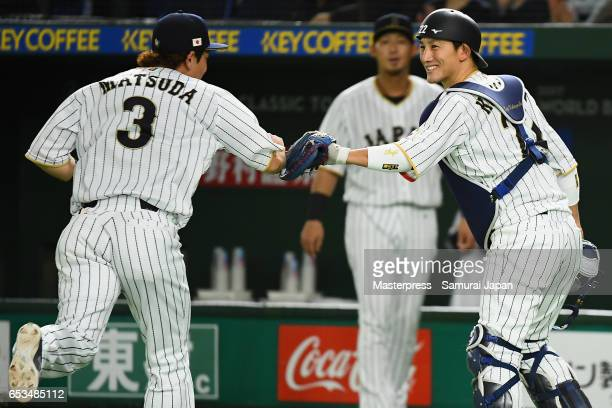 Infielder Nobuhiro Matsuda high fives with Catcher Seiji Kobayashi after the top of the second inning during the World Baseball Classic Pool E Game...