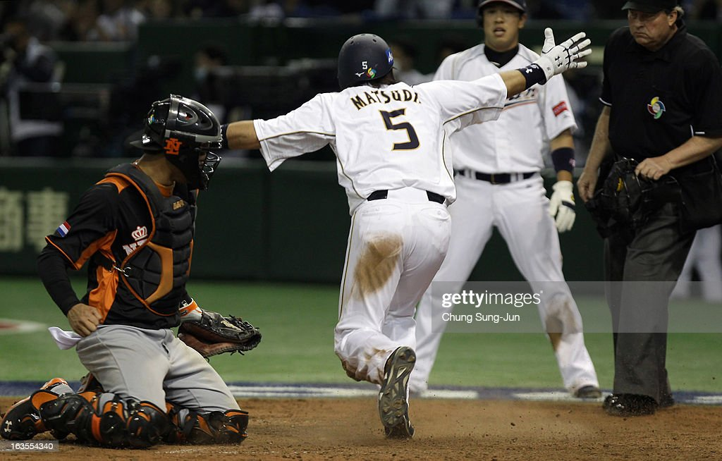 Infielder <a gi-track='captionPersonalityLinkClicked' href=/galleries/search?phrase=Nobuhiro+Matsuda&family=editorial&specificpeople=8673842 ng-click='$event.stopPropagation()'>Nobuhiro Matsuda</a> # 5 of Japan safely reaches home base as catcher Quintin De Cuba #23 of Netherlands looks on in the eighth inning during the World Baseball Classic Second Round Pool 1 game between Japan and the Netherlands at Tokyo Dome on March 12, 2013 in Tokyo, Japan.