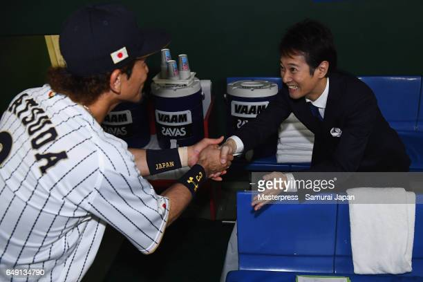 Infielder Nobuhiro Matsuda of Japan shakes hands with tv personality Masahiro Nakai after the World Baseball Classic Pool B Game One between Cuba and...