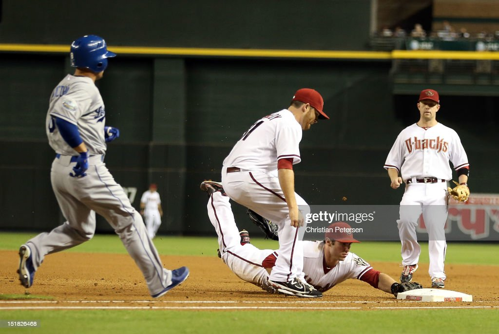 Infielder Paul Goldschmidt of the Arizona Diamondbacks dives into first base to complete a ground ball out hit by Shane Victorino of the Los Angeles...