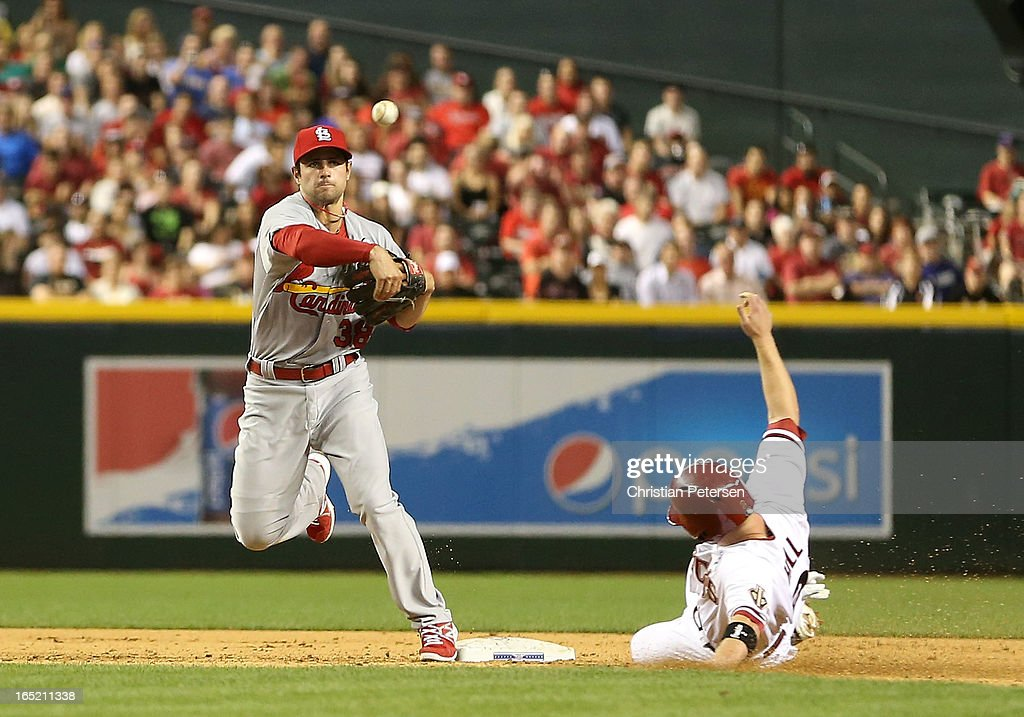 Infielder Pete Kozma #38 of the St. Louis Cardinals throws over the sliding Aaron Hill #2 of the Arizona Diamondbacks to complete a fifth inning double play during the MLB Opening Day game at Chase Field on April 1, 2013 in Phoenix, Arizona.