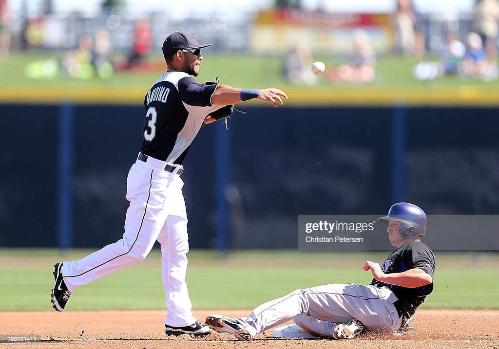 Infielder Robert Andino #3 of the Seattle Mariners throws over the sliding Jordan Pacheco #15 of the Colorado Rockies as he attempts an unsuccessful double play during the first inning of the spring training game at Peoria Stadium on March 4, 2013 in Peoria, Arizona.