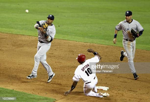 Infielder Robinson Cano of the New York Yankees throws over the sliding Justin Upton of the Arizona Diamondbacks to complete a double play during the...