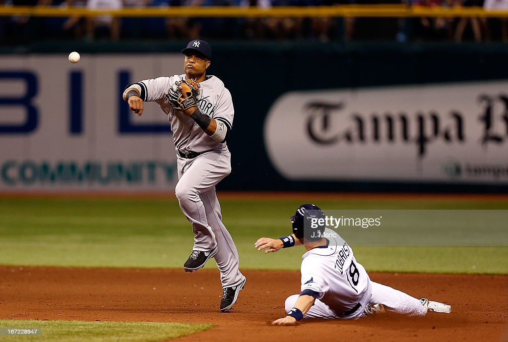 Infielder <a gi-track='captionPersonalityLinkClicked' href=/galleries/search?phrase=Robinson+Cano&family=editorial&specificpeople=538362 ng-click='$event.stopPropagation()'>Robinson Cano</a> #24 of the New York Yankees turns a double play as <a gi-track='captionPersonalityLinkClicked' href=/galleries/search?phrase=Ben+Zobrist&family=editorial&specificpeople=2120037 ng-click='$event.stopPropagation()'>Ben Zobrist</a> #18 of the Tampa Bay Rays tries to break it up during the game at Tropicana Field on April 22, 2013 in St. Petersburg, Florida.