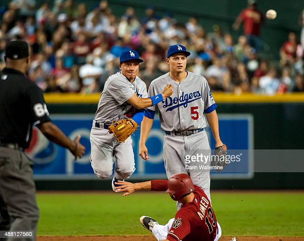 Infielder Ronald Torreyes of the Los Angeles Dodgers throws over Nick Ahmed of the Arizona Diamondbacks in a double play attempt as Corey Seager...