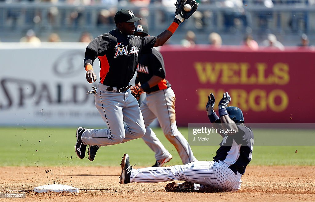 Infielder Ronnier Mustelier #97 of the New York Yankees steals second as shortstop <a gi-track='captionPersonalityLinkClicked' href=/galleries/search?phrase=Adeiny+Hechavarria&family=editorial&specificpeople=6926508 ng-click='$event.stopPropagation()'>Adeiny Hechavarria</a> #3 of the Miami Marlins takes the throw during a Grapefruit League Spring Training Game at George M. Steinbrenner Field on March 15, 2013 in Tampa, Florida.