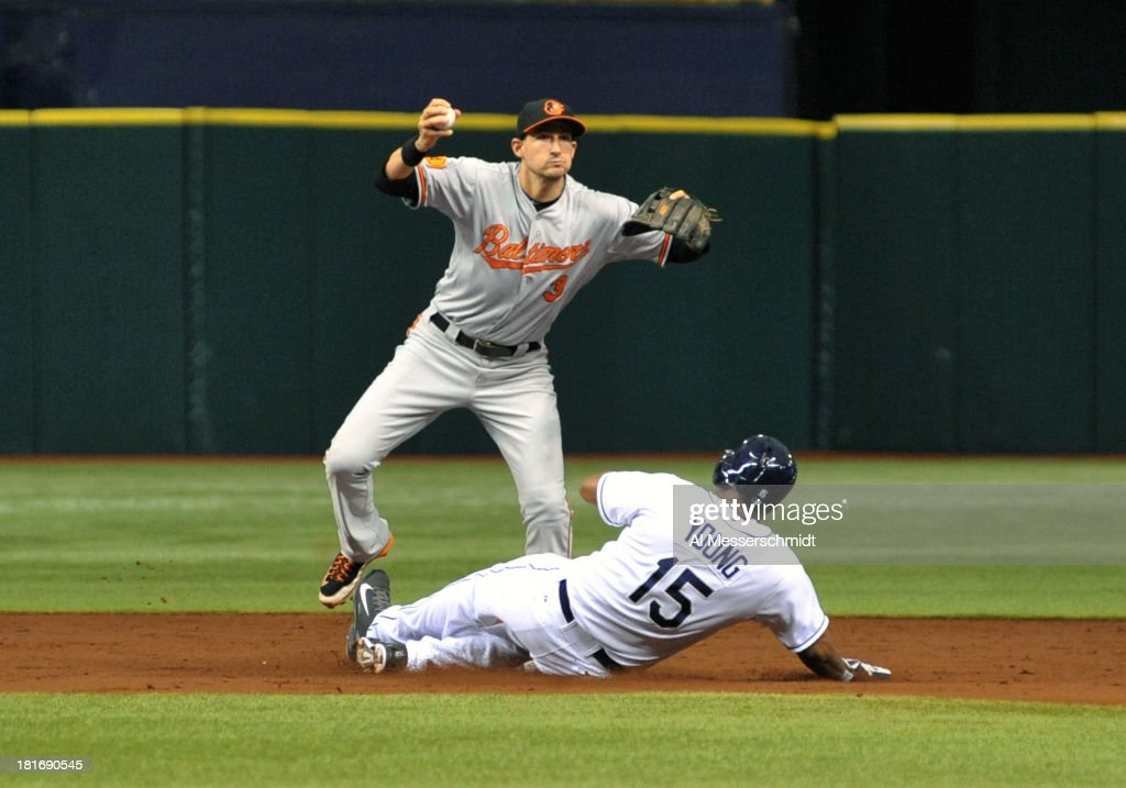 Infielder Ryan Flaherty #3 of the Baltimore Orioles holds a ball at 2nd base as designated hitter Delmon Young #15 of the Tampa Bay Rays slides September 23, 2013 at Tropicana Field in St. Petersburg, Florida.