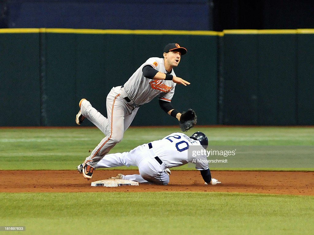 Infielder <a gi-track='captionPersonalityLinkClicked' href=/galleries/search?phrase=Ryan+Flaherty&family=editorial&specificpeople=4412528 ng-click='$event.stopPropagation()'>Ryan Flaherty</a> #3 of the Baltimore Orioles throws to second base over sliding infielder Matt Joyce #20 of the Tampa Bay Rays September 23, 2013 at Tropicana Field in St. Petersburg, Florida.
