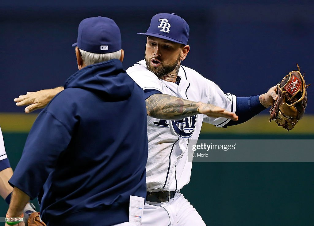 Infielder Ryan Roberts #19 of the Tampa Bay Rays celebrates with manager Joe Maddon #70 after the Rays victory over the New York Yankees at Tropicana Field on September 4, 2012 in St. Petersburg, Florida.