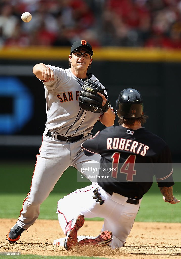 Infielder <a gi-track='captionPersonalityLinkClicked' href=/galleries/search?phrase=Ryan+Theriot&family=editorial&specificpeople=796597 ng-click='$event.stopPropagation()'>Ryan Theriot</a> #5 of the San Francisco Giants throws over the sliding Ryan Roberts #14 of the Arizona Diamondbacks to complete a double play during the sixth inning of the MLB game at Chase Field on April 7, 2012 in Phoenix, Arizona.