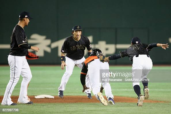 Infielder Ryosuke Kikuchi of Japan tags out Infielder Juremi Profar of the Netherlands in a rundown in the third inning during the international...
