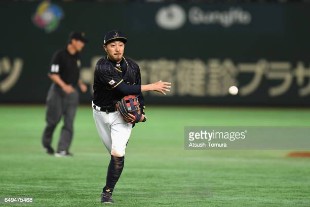 Infielder Ryosuke Kikuchi of Japan tosses to the first base in the bottom of the fourth inning during the World Baseball Classic Pool B Game Three...
