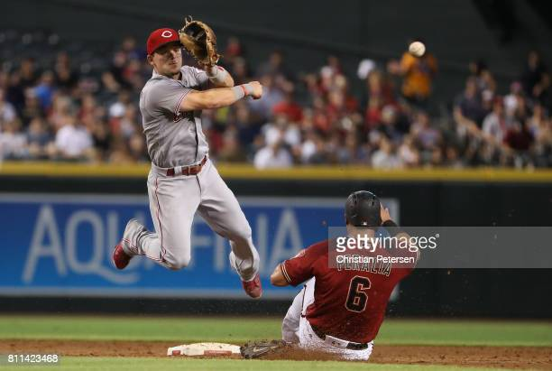Infielder Scooter Gennett of the Cincinnati Reds throws over the sliding David Peralta of the Arizona Diamondbacks to compete a double play during...
