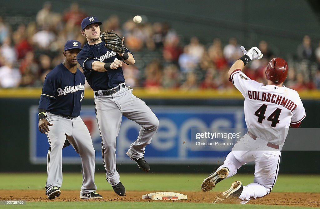 Infielder Scooter Gennett of the Milwaukee Brewers throws over the sliding Paul Goldschmidt of the Arizona Diamondbacks to complete a double play...