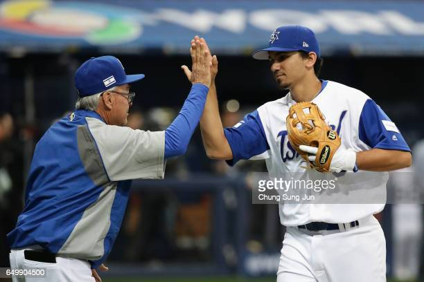 Infielder Scott Burcham of Israel high fives with Manager Jerry Weinstein after the World Baseball Classic Pool A Game Five between Netherlands and...