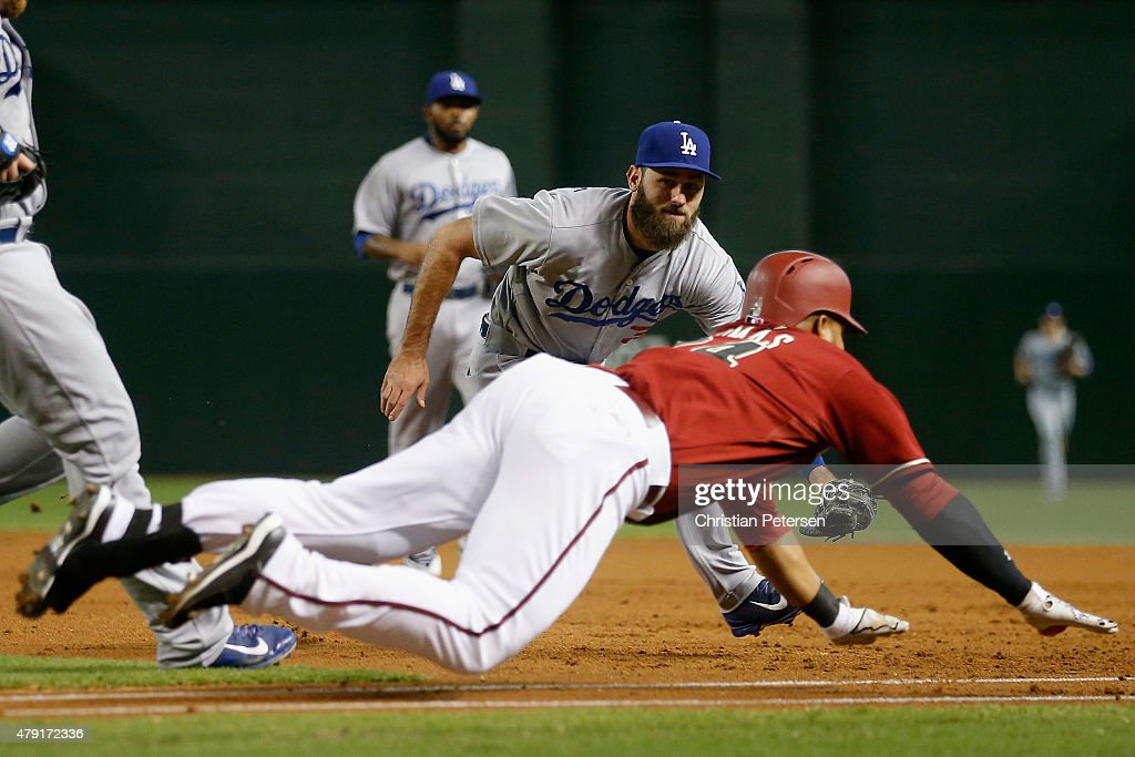 Infielder <a gi-track='captionPersonalityLinkClicked' href=/galleries/search?phrase=Scott+Van+Slyke&family=editorial&specificpeople=9008639 ng-click='$event.stopPropagation()'>Scott Van Slyke</a> #33 of the Los Angeles Dodgers reaches to tag out the diving Yasmany Tomas #24 of the Arizona Diamondbacks during the first inning of the MLB game at Chase Field on July 1, 2015 in Phoenix, Arizona.
