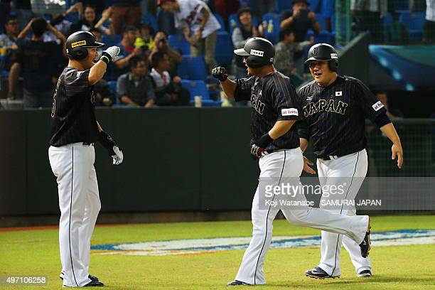 Infielder Sho Nakata of Japan is congratulated on hitting a threerun homerun with his team mates Yoshitomo Tsutsugo and Takeya Nakamura in the top of...