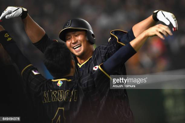 Infielder Sho Nakata of Japan celebrates with his team mate infielder Ryosuke Kikuchi after hitting a solo homer in the top of the seventh inning...