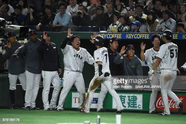 Infielder Shuta Tonosaki of Japan high fives with team mates after scoring a run during the Eneos Asia Professional Baseball Championship 2017 final...