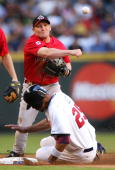 Infielder Stubby Clapp of Team Canada throws over Derrek Lee of Team USA to complete a double play during the Round 1 Pool B Game of the World...