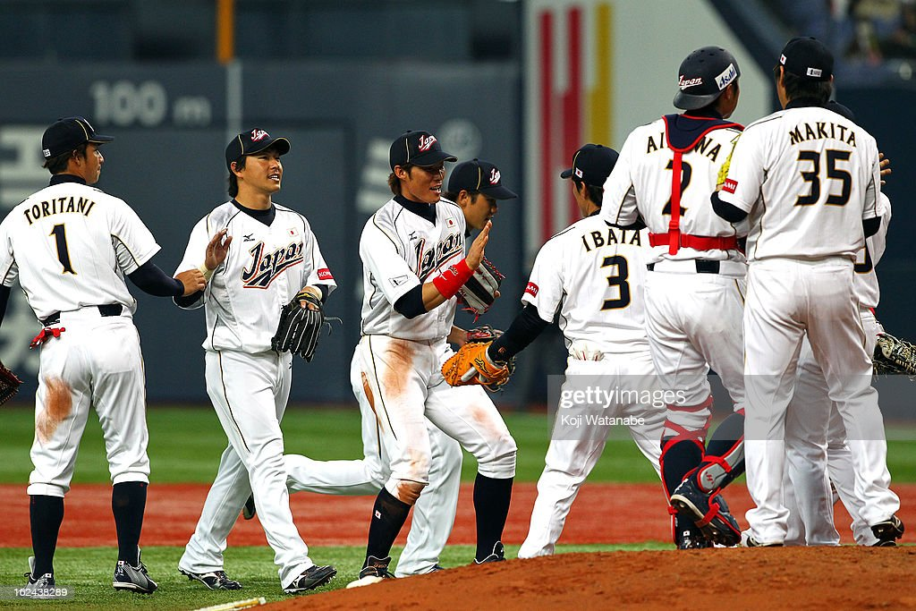 Infielder Takashi Toritani #1 and Outfielder Hisayoshi Chono #34 and Outfielder Yoshio Itoi #9 of Japan celebrates with team mates after defeating international friendly game between Japan and Australia at Kyocera Dome Osaka on February 23, 2013 in Osaka, Japan.