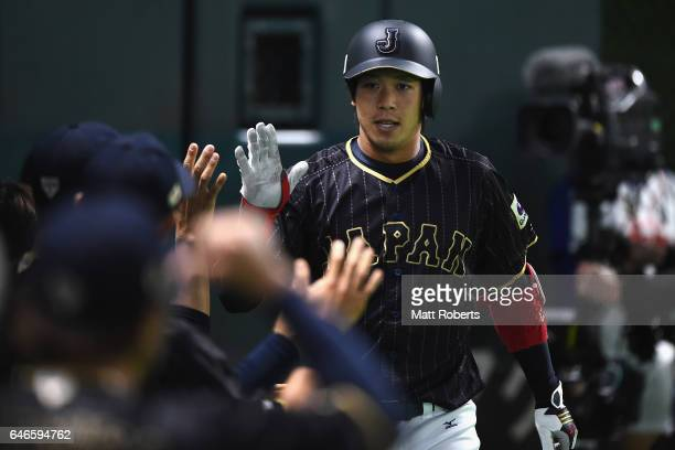 Infielder Tetsuto Yamada of Japan high fives with his team mates after hitting a solo homer in the top of the first inning during the SAMURAI JAPAN...
