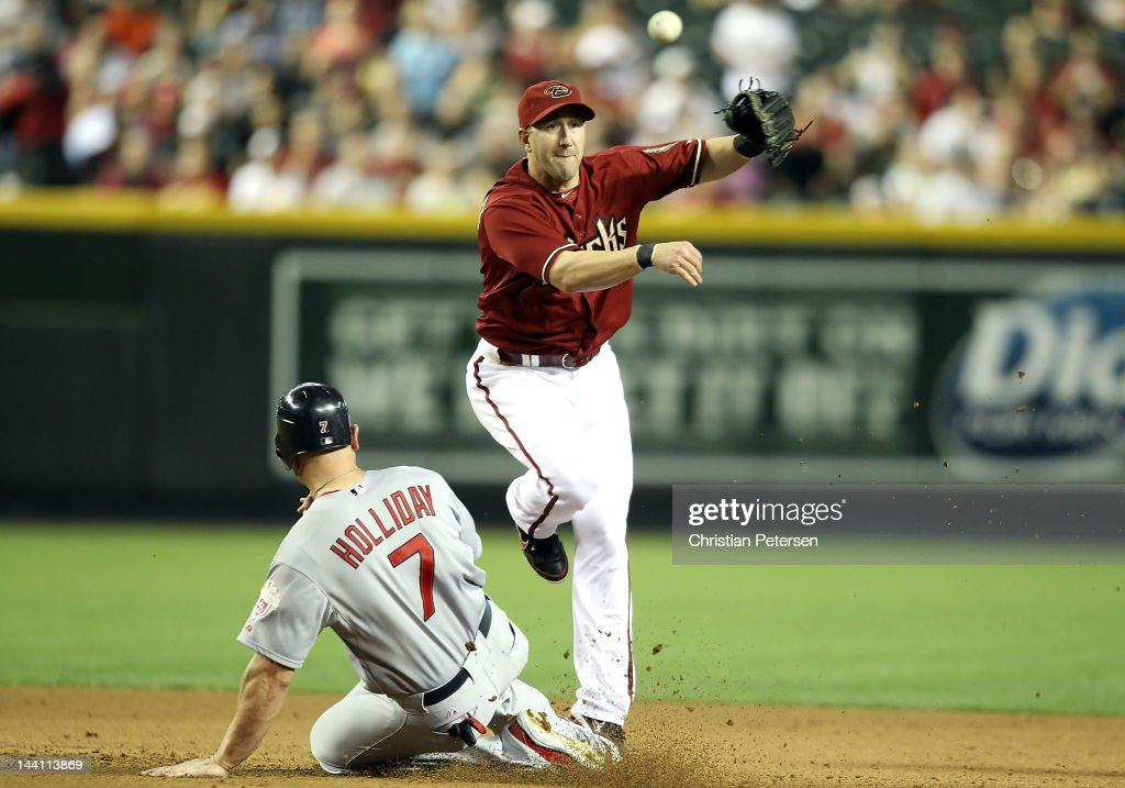 Infielder Willie Bloomquist #18 of the Arizona Diamondbacks throws over the sliding Matt Holliday #7 of the St Louis Cardinals to complete a double play during the fifth inning of the MLB game at Chase Field on May 9, 2012 in Phoenix, Arizona.
