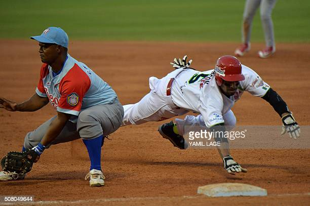 Infielder Yorelbis Charles of Cuba makes an out on first base against Chris Roberson of Mexico during their 2016 Caribbean baseball series game on...