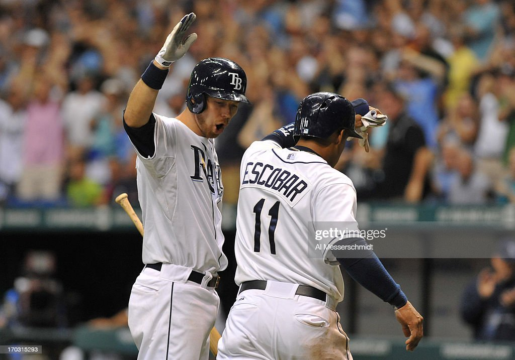 Infielder <a gi-track='captionPersonalityLinkClicked' href=/galleries/search?phrase=Yunel+Escobar&family=editorial&specificpeople=757358 ng-click='$event.stopPropagation()'>Yunel Escobar</a> #11 of the Tampa Bay Rays celebrates with infielder <a gi-track='captionPersonalityLinkClicked' href=/galleries/search?phrase=Ben+Zobrist&family=editorial&specificpeople=2120037 ng-click='$event.stopPropagation()'>Ben Zobrist</a> #18 after scoring a run against the Boston Red Sox June 10, 2013 at Tropicana Field in St. Petersburg, Florida.