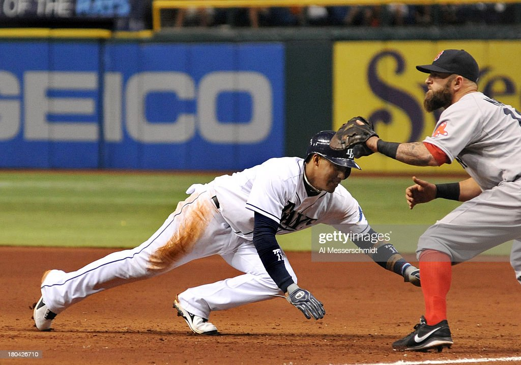 Infielder <a gi-track='captionPersonalityLinkClicked' href=/galleries/search?phrase=Yunel+Escobar&family=editorial&specificpeople=757358 ng-click='$event.stopPropagation()'>Yunel Escobar</a> #11 of the Tampa Bay Rays dives into 1st base to avoid a pickoff against the Boston Red Sox September 12, 2013 at Tropicana Field in St. Petersburg, Florida.